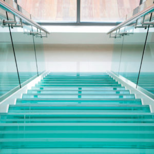 Modern glass stairs in plush apartment. light and airy high key feel.